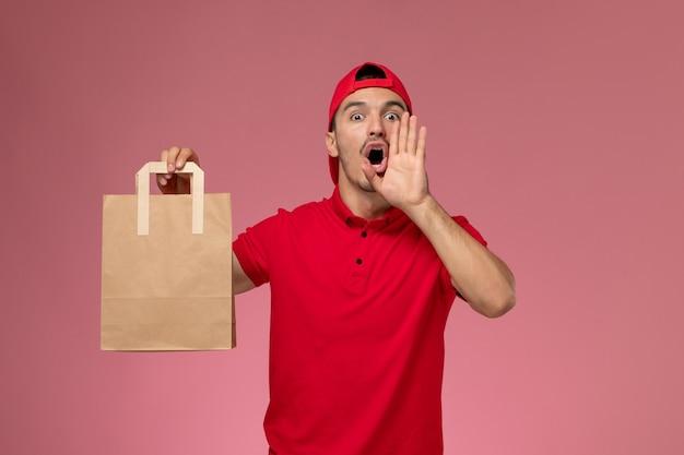 淡いピンクの背景に紙の食品パッケージを保持している赤い制服の岬の正面図の若い男性の宅配便。