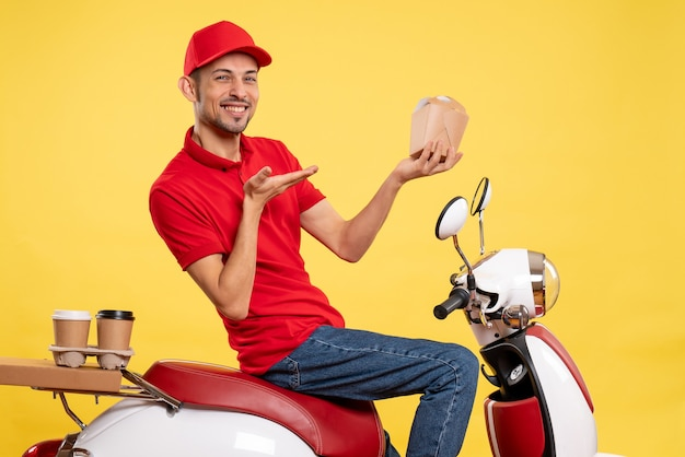 Вид спереди молодой мужчина-курьер в красной форме, держащий доставку еды на желтом фоне