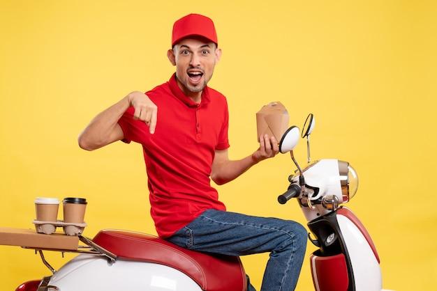 黄色の背景に配達食品を保持している赤い制服の正面図若い男性宅配便