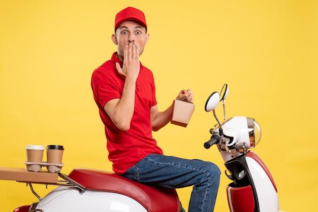 Вид спереди молодой курьер-мужчина в красной форме с доставкой еды на желтом фоне