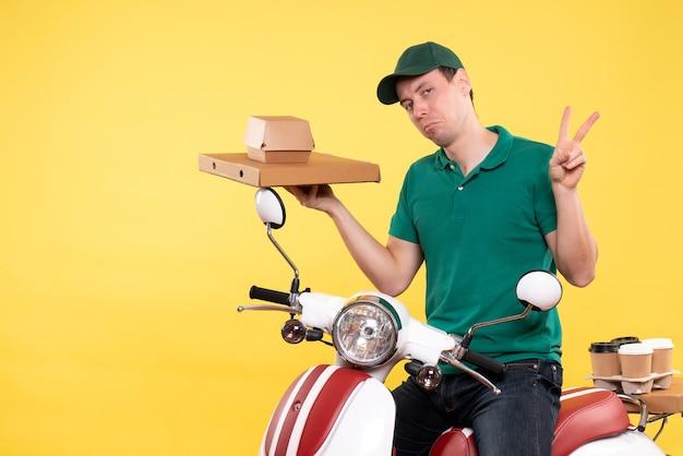 노란색에 음식 패키지를 들고 제복을 입은 전면보기 젊은 남성 택배