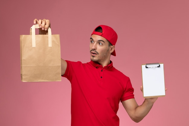 Front view young male courier in red uniform cape holding food package and notepad smiling on the pink background.