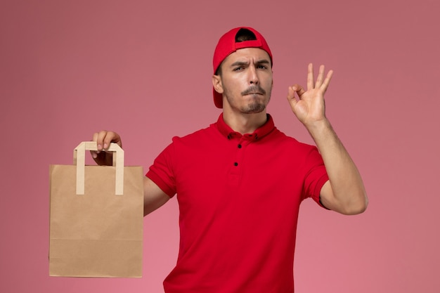 Front view young male courier in red uniform cape holding paper food package on pink background.