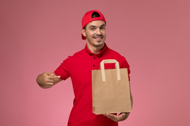 Front view young male courier in red uniform cape holding paper food package on the pink background.
