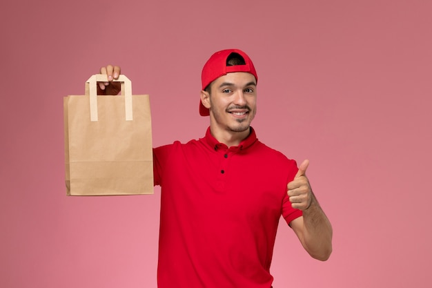 Front view young male courier in red uniform cape holding paper food package smiling on the light pink background.