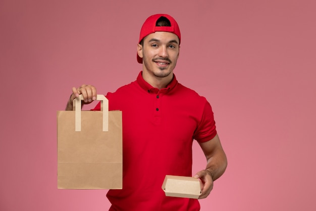 Front view young male courier in red uniform cape holding two different food packages with smile on pink background.