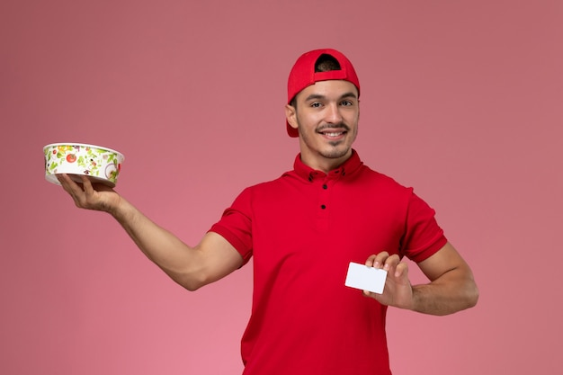 Front view young male courier in red uniform cape holding white plastic card and delivery bowl on light-pink background.