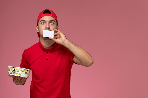 Front view young male courier in red uniform cape holding white plastic card and delivery bowl on light pink background.