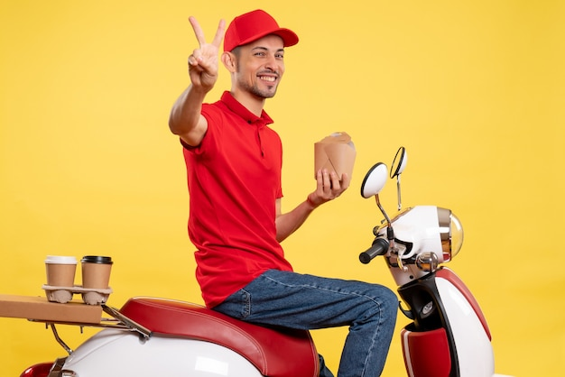 Corriere maschio giovane di vista frontale in cibo di consegna uniforme rosso della tenuta su fondo giallo