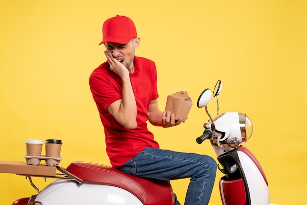 Front view young male courier in red uniform suffering from toothache on yellow background