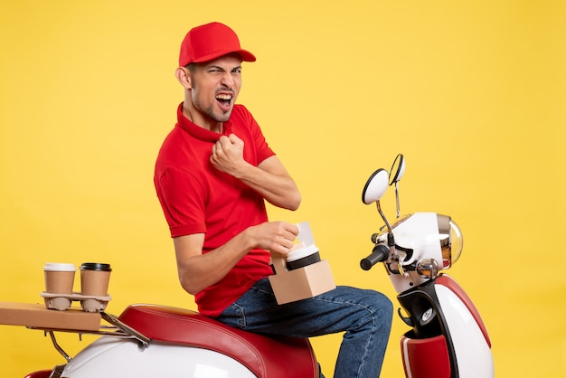 Front view young male courier in red uniform with coffee on yellow background