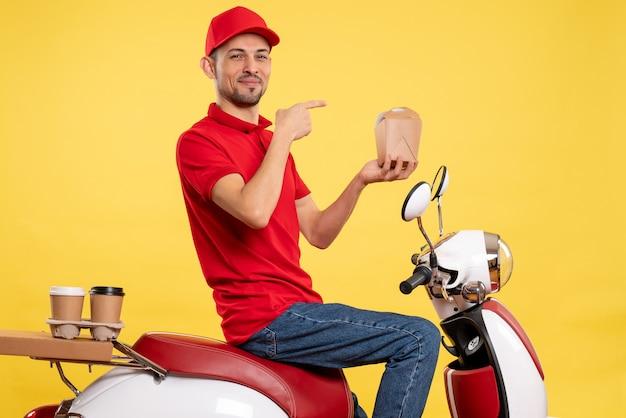 Corriere maschio giovane vista frontale in uniforme rossa con cibo di consegna su sfondo giallo