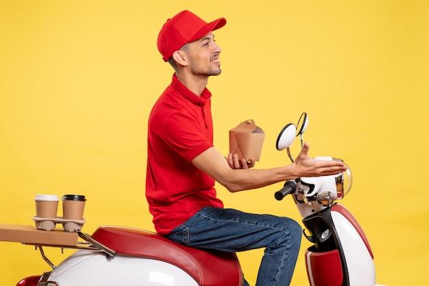Corriere maschio giovane vista frontale in uniforme rossa con poco cibo di consegna su sfondo giallo