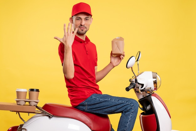 Front view young male courier in red uniform on yellow background