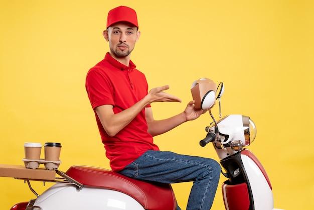 Corriere maschio giovane vista frontale in uniforme rossa su sfondo giallo