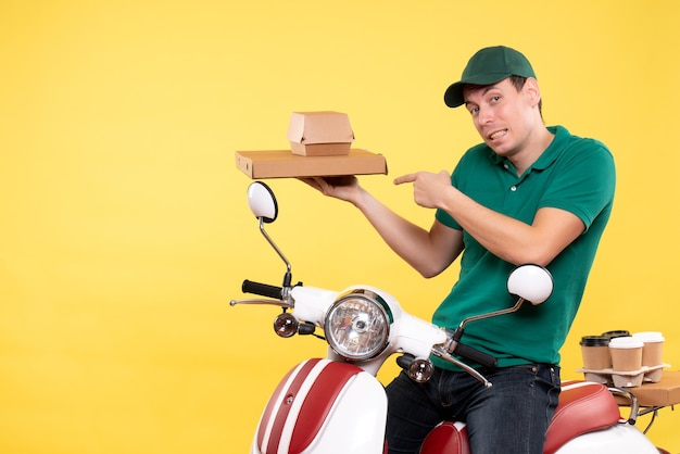 Front view young male courier in uniform holding food packages on a yellow