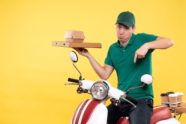 Front view young male courier in uniform holding food packages on yellow