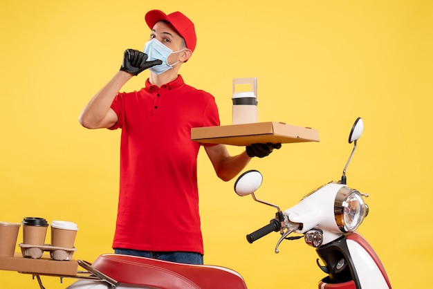 Corriere maschio giovane vista frontale in uniforme con scatola di cibo e caffè su sfondo giallo