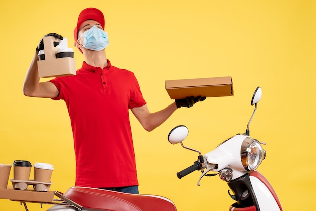 Front view young male courier in uniform with coffee and food box on yellow background