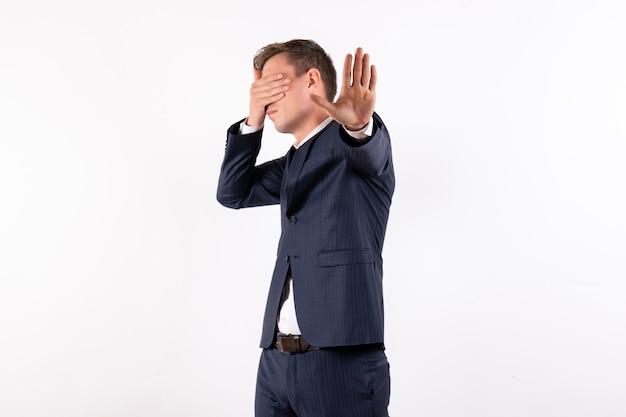 白い背景の感情の古典的な厳格なスーツで彼の顔を覆っている正面図若い男性人間のファッションモデルスーツ男性