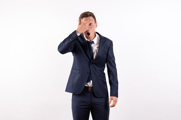 白い背景の上の古典的な厳格なスーツで彼の顔を覆っている正面図若い男性ファッション感情人間モデルスーツ男性