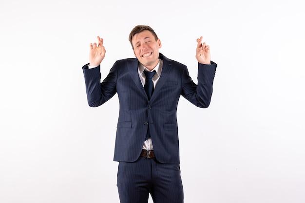 正面図若い男性が白い背景の感情に古典的な厳格なスーツで彼の指を交差させる人間のファッションモデルスーツ男性