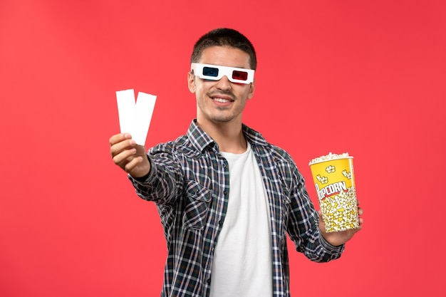 Front view young male in -d sunglasses holding popcorn package and tickets on light-red wall cinema movie theater film male