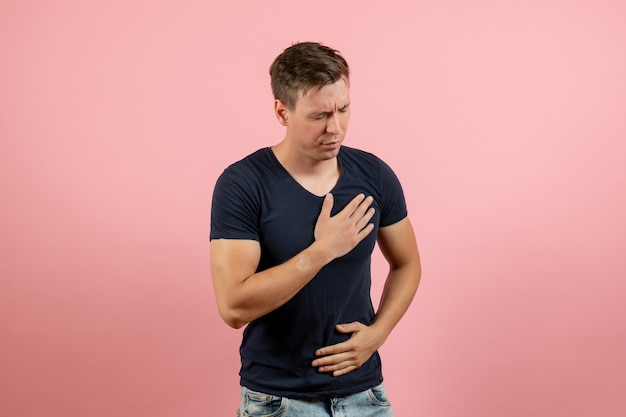 Front view young male in dark-blue shirt having troubles with heart on pink background male human color man model emotions