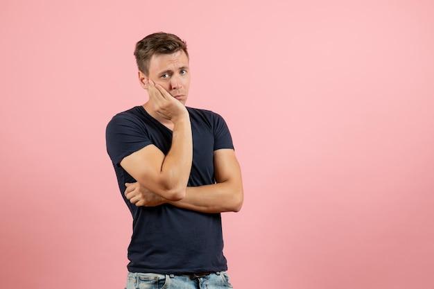 Vista frontale giovane maschio in camicia blu scuro in posa e sentirsi depresso su sfondo rosa