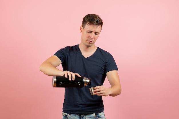 Vista frontale giovane maschio in camicia blu scuro che versa acqua dal thermos su sfondo rosa