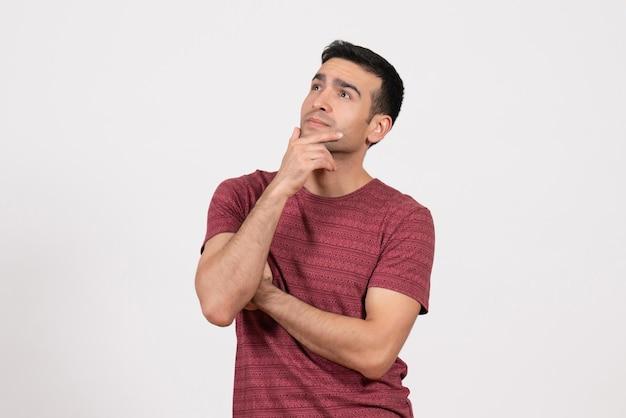 Vista frontale giovane maschio in maglietta rosso scuro in piedi e pensando su sfondo bianco