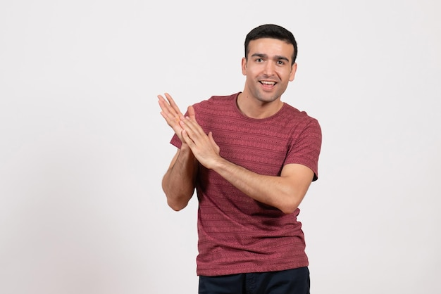 Front view young male in dark-red t-shirt standing on white background