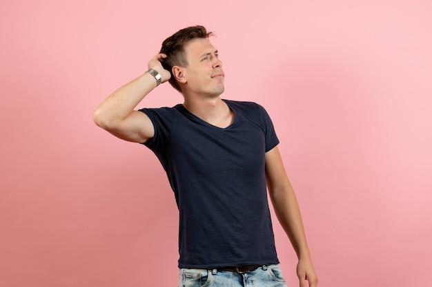 Giovane maschio di vista frontale in maglietta e jeans scuri che pensano su fondo rosa