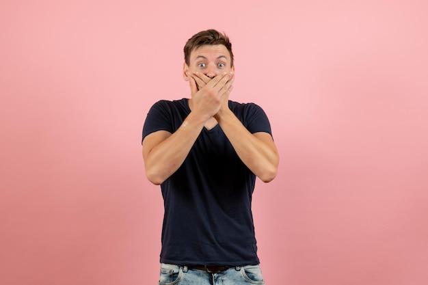 Vista frontale giovane maschio in maglietta scura in posa scioccato su sfondo rosa