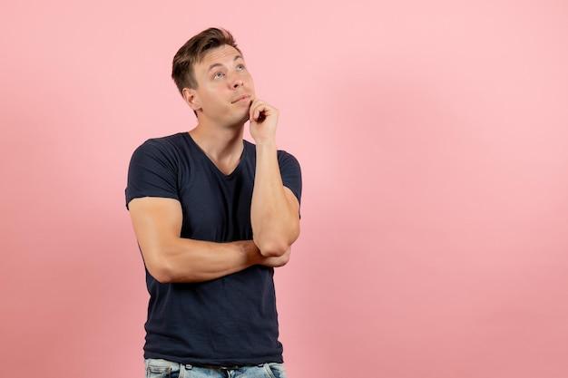 Vista frontale giovane maschio in maglietta scura in posa e pensando su sfondo rosa
