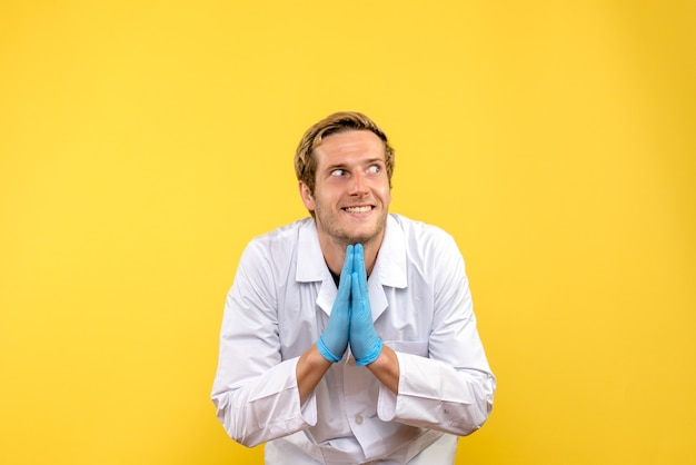 Front view young male doctor excited on yellow background human medic covid- pandemic