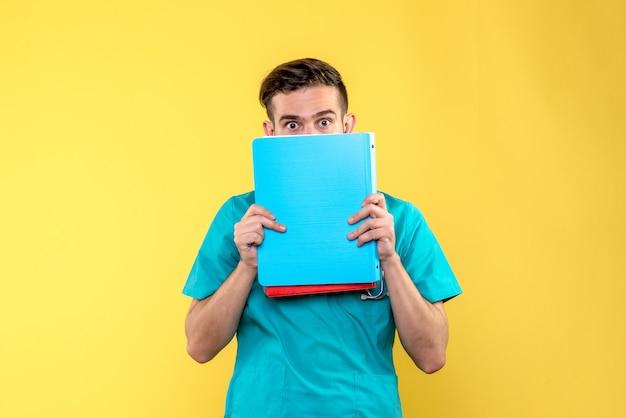 Vista frontale del giovane medico maschio che tiene analisi sulla parete giallo chiaro