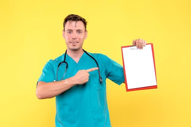 Vista frontale del giovane medico maschio che tiene analisi sulla parete gialla