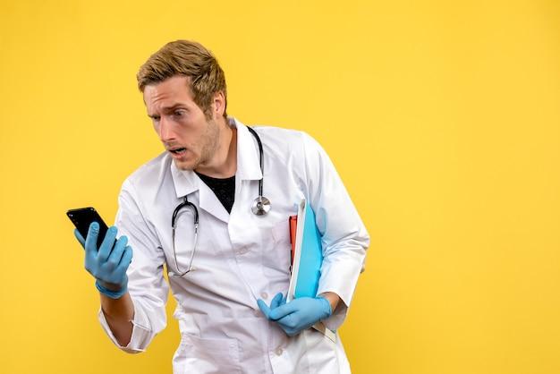 Вид спереди молодой мужчина-врач держит телефон на желтом фоне вирус здоровья медик человека