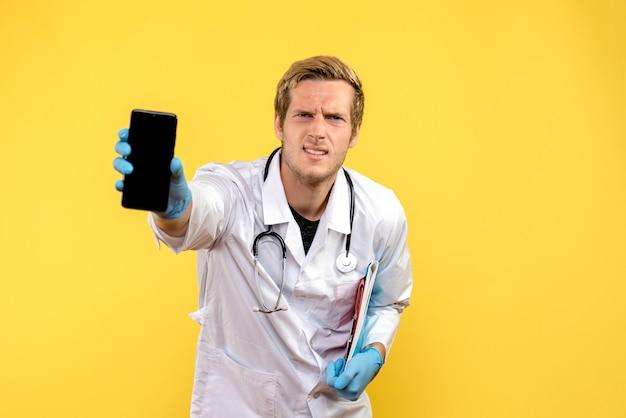 Вид спереди молодой мужчина-врач, держащий телефон на желтом столе, медицинский медик, человеческий вирус