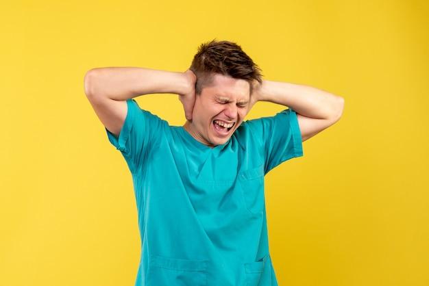 黄色の背景に彼の耳を閉じる医療スーツの若い男性医師の正面図