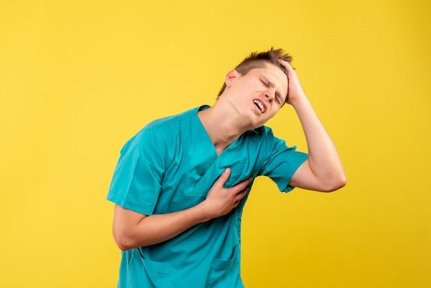 Вид спереди молодой мужчина-врач в медицинском костюме с болью в сердце на желтом фоне