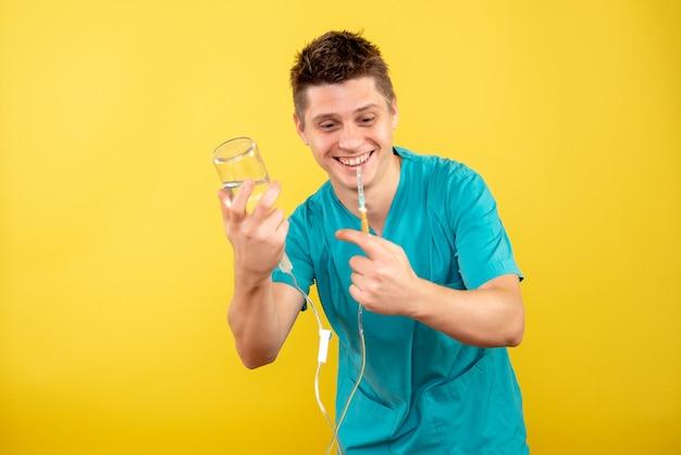 Вид спереди молодой мужчина-врач в медицинском костюме, держащий капельницу на желтом фоне