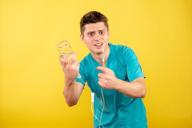 노란색 배경에 dropper를 들고 의료 소송에서 전면보기 젊은 남성 의사