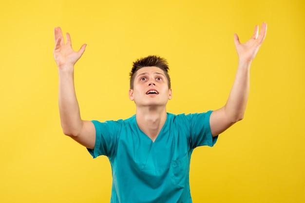 노란색 배경에 의료 소송에서 전면보기 젊은 남성 의사