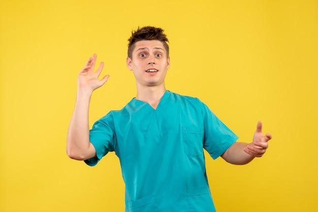 Вид спереди молодой мужчина-врач в медицинском костюме на желтом фоне