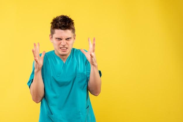 黄色の背景に医療スーツを着た若い男性医師の正面図