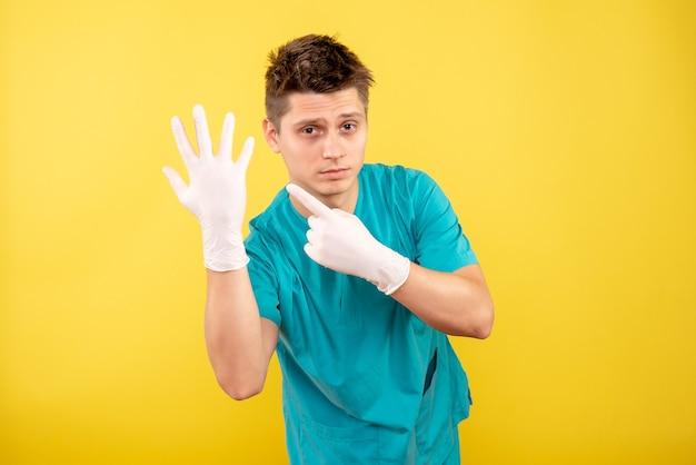 黄色の背景に手袋を着用した医療スーツの若い男性医師の正面図