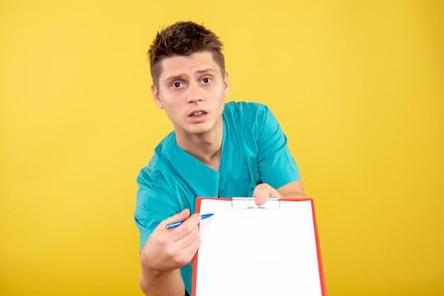 노란색 배경에 메모 및 분석 의료 소송에서 전면보기 젊은 남성 의사