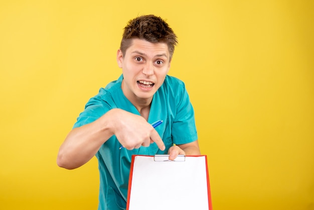 Вид спереди молодой мужчина-врач в медицинском костюме с запиской и анализом на желтом фоне